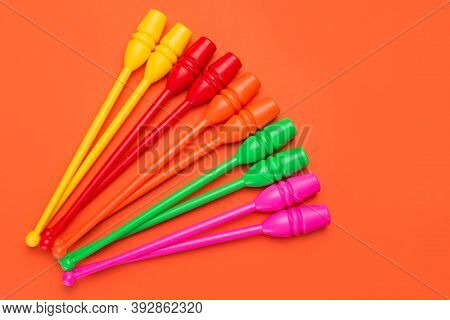 Five Pairs Of Colored Gymnastic Clubs, Lie On An Orange Background, Concept