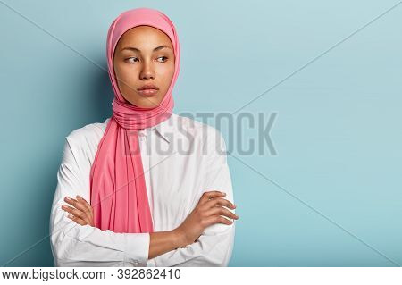 Good Looking Thoughtful Female With Dark Skin, Contemplates About Something, Keeps Hands Crossed, We