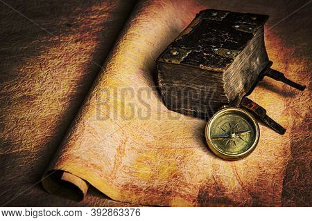 Ancient sailor diary lying together with brass compass on an old grungy parchment. Still life good for navigation or pirate topics