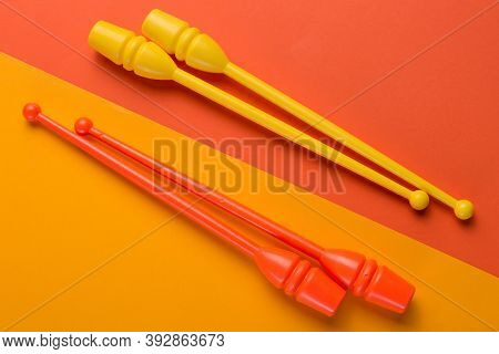 Two Pairs Of Colored Gymnastic Clubs, On Orange And Yellow Background, Diagonal Arrangement