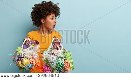 Responsible Frightened Woman With Scared Expression, Holds Bags With Plastic Straws And Bottles, Stu