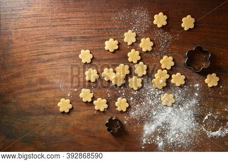 Small flower shape cookies, cookie-cutter and sprinkled floor scattered on the wooden background. Cookies are ready to be fried.