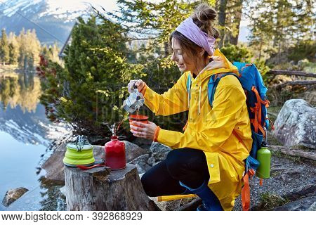 Satisfied Female Traveler Pours Coffee From Coffeemaker In Teacup, Uses Red Camping Butane Bottle, W