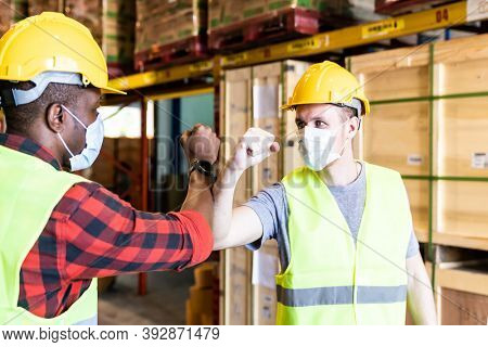 Interracial warehouse worker with face mask do elbow bump for alternative greeting after factory reopen from city lockdown cause of coronavirus COVID-19 pandemic.