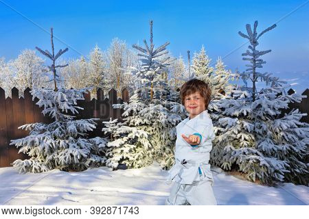 Handsome boy training for judo. Frosty snowy sunny day in the winter forest. The northern winter sun is low above the horizon. New Years is soon