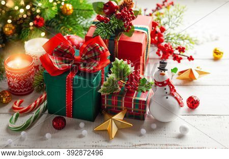 Winter composition with Christmas gift boxes, holiday sweets and Christmas decorations on wooden table.