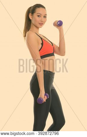 Studio Shot Of Young Beautiful Asian Woman Standing While Exercising Dumbbells Ready For Gym