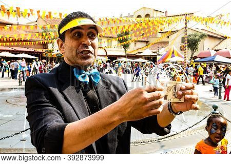 Street Magician Performing Tricks And Magic Show For Children At Funfair