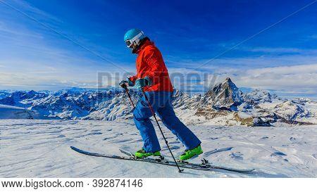 Man backcountry skiing on fresh powder snow with Matterhorn in background, Zermatt in Swiss Alps.