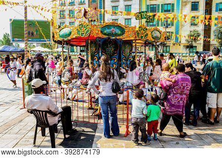 Kids Riding On Fairground Carousel Merry-go-round Out Outdoor Funfair