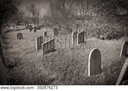 Tombstones, Graveyard With Tombstones, Field Of Old Abandoned Tombstones. In Black And White