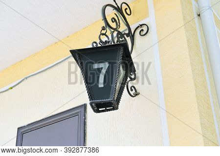 House Number Sign In A Shape Of Old Streetlight. Metallic Lantern With Digit 7 On It Hangin On A Hou