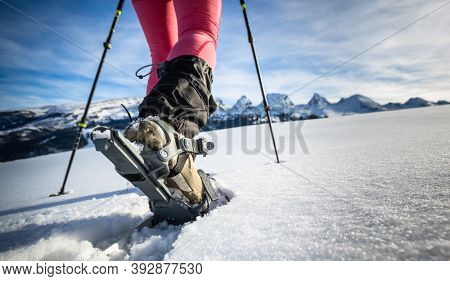 Young woman snowshoeing in high mountains, enjoying a lovely day