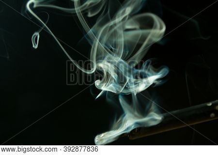 Soldering Iron With Smoke From The Sting Of Burning Rosin. Photo On A Black Background