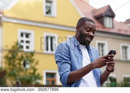 Handsome Afro-american Man Using Smartphone And Smiling. Happy Man Using Mobile Phone Apps, Texting