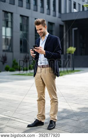 Handsome Businessman Using Smartphone And Smiling. Happy Young Man Using Mobile Phone Apps, Texting