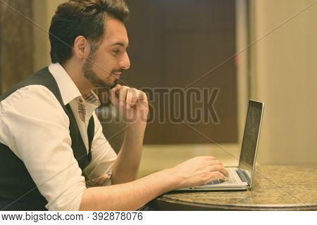 Profile View Of Young Handsome Indian Man Thinking While Using Laptop In The Lobby Of Hotel
