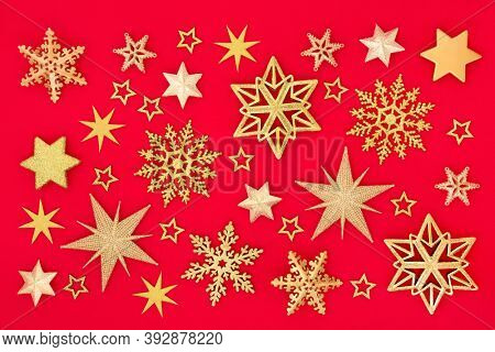 Christmas composition of gold snowflake & star on red background. Abstract design for xmas New Year & holiday season. Flat lay top view.