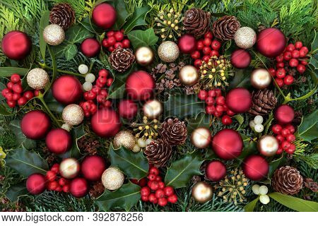 Christmas festive background scene with red & gold baubles & winter greenery of holly, ivy, mistletoe, cedar cypress leaves & pine cones. Xmas composition for the holiday season,. Flat lay, top view.
