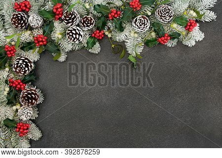 Festive winter solstice snow covered spruce fir border with holly, mistletoe & pine cones on grey grunge. Composition for Christmas & New Year holiday season. Top view, flat lay, copy space.