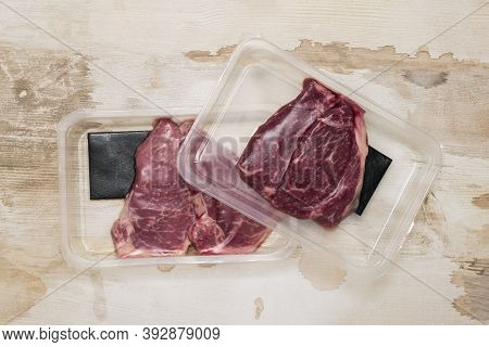 Two Vacuum Packages With Beef Steaks On A Wooden Background. Sealed Packaging For Meat.