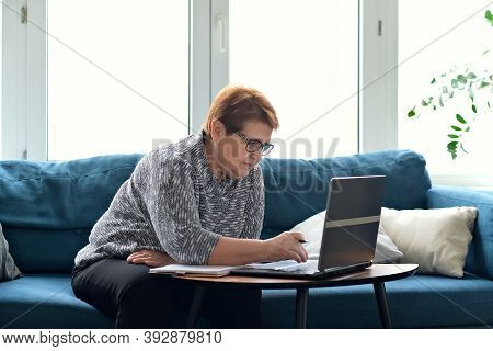 Senior Woman Using Laptop For Websurfing. The Concept Of Senior Employment, Social Security. Mature
