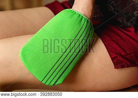 Woman Massages Thigh With Green Terry Washcloth With Mittens