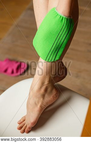 Woman Massages Leg With Green Terry Washcloth With Mittens