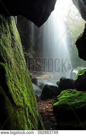 Forty Foot Falls Seen Through The Narrow Cave, Bright Green Moss Growing On The Rocks And Spider Web