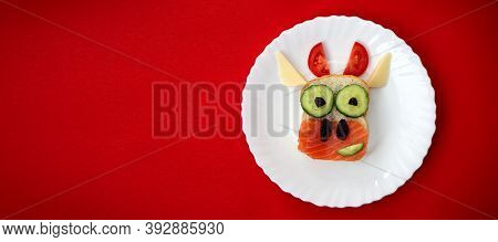 Funny Sandwich With Edible Symbol Of 2021 Bull Cow Made From Toast Bread, Red Fish, Cucumber, Tomato
