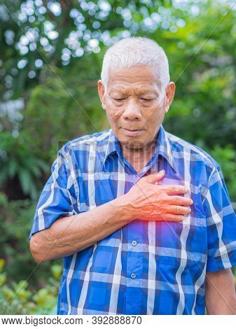 Senior Man Having A Heart Attack. Elderly Asian Man Clutching His Chest In Pain At The First Signs O
