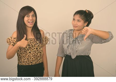Young Happy Persian Woman Smiling While Giving Thumb Up With Young Fat Persian Teenage Girl Thinking