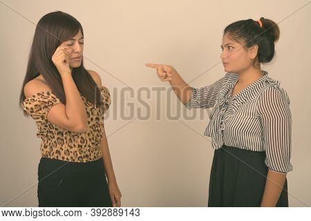 Studio Shot Of Young Angry Fat Persian Teenage Girl Pointing At Young Persian Woman Crying Against G