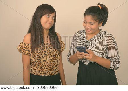 Studio Shot Of Young Persian Woman Looking Angry At Young Happy Fat Persian Teenage Girl Smiling Whi
