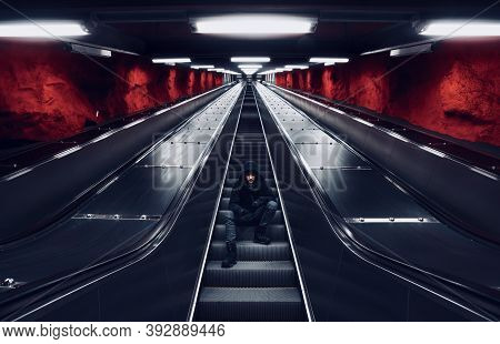 Mysterious Man With Black Hood Is Sitting On The Escalators Stair In Underground Station With Rocky