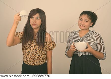 Young Persian Woman Holding Empty Coffee Cup Upside Down With Young Happy Fat Persian Teenage Girl H