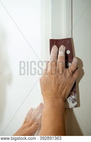 A Close Up Of Woman Hands Is Sanding Wall
