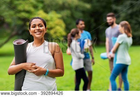 fitness, sport and healthy lifestyle concept - happy smiling young african american woman with mat over group of people meeting for yoga class at summer park