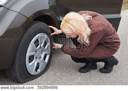 A Young Blonde Woman Stands Near Her Car With A Flat Tire, Trouble On The Road.