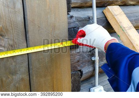 Male Hands In Work Gloves With A Yellow Tape Measure Against A Background Of Dark Boards Measure The