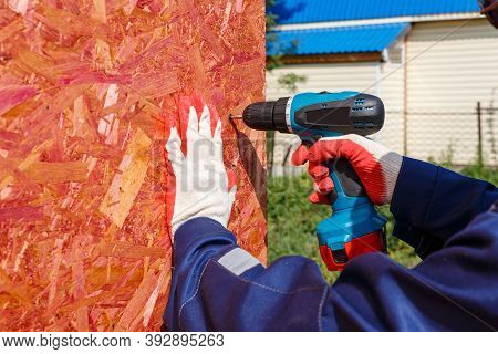 Gloved Men Hold A Screwdriver And A Wooden Panel. Fastening The Panel To The Wall With A Screw And C