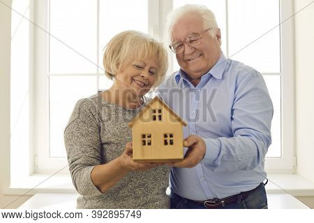 Smiling Senior Couple Holding Miniature House Standing By The Window In Their New Home