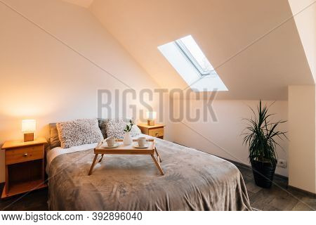 Small Attic Bedroom In A Family House With Morning Breakfast Service On The Bed. The Bed Also Has A