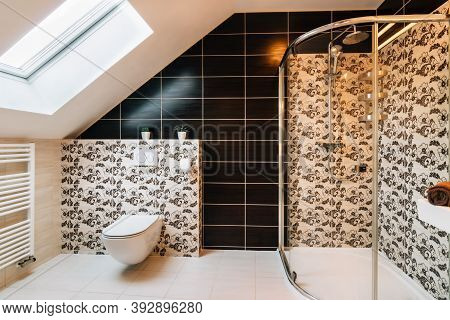 Small Attic Bathroom With Skylight. The Tiling Is In Brown Colors Variegated With Texture Of Leaves.