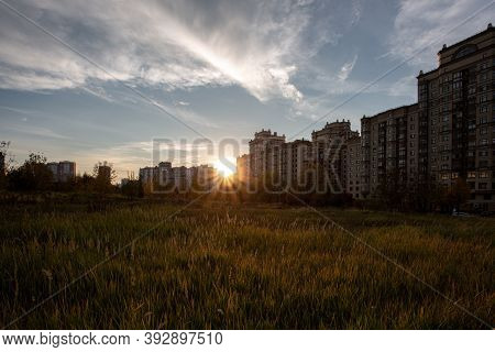 Sunset Over An Old Settlement. On The Right Side Are Tall Apartment Buildings With The Setting Sun.
