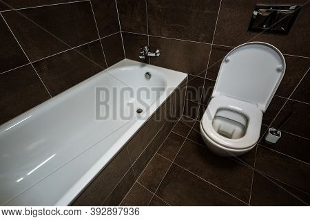 Detail Of A Small Bathroom With A Bathtub And A Toilet Next To Each Other. The Toilet Is Modern With