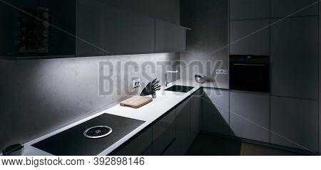 Modern Kitchen In Minimalist Design During Night With Led Light Strip, Modern Appliances And Premium
