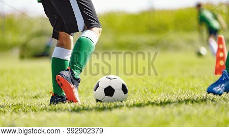 Closeup Image Of Soccer Player Legs And Soccer Ball On The Field. Fotballers On Practice Training Le