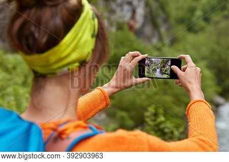 Backwards Shot Of Woman Tourist Makes Photo Of River In Ravine On Smartphone Device For Posting In S