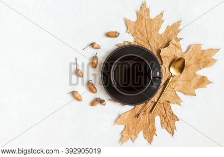 Autumn Still Life With A Black Coffee, Leaves And Acorns On A White Background. Acorn Coffee In A Bl